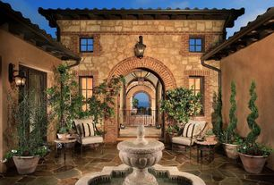 Mediterranean Patio with Welcome Garden Pineapple Tiered Outdoor Fountain, Fountain, French doors, Arched doorway, Courtyard