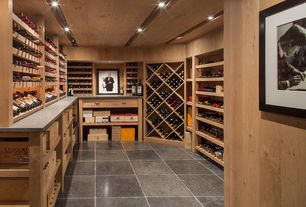Contemporary Wine Cellar with can lights, stone tile floors, Standard height