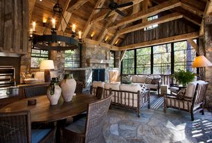 Country Great Room with Wall sconce, Rustic lodge hickory sofa, Columns, limestone floors, Exposed beam, Built-in bookshelf