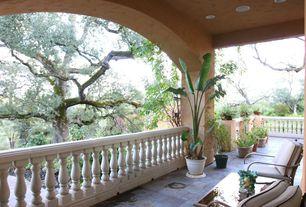 Mediterranean Porch with exterior stone floors, Wrap around porch, Fence