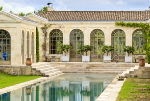 Traditional Swimming Pool with exterior stone floors, Arched window, Raised beds