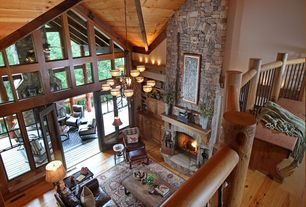 Rustic Great Room with Rough cut stone fireplace, Pine flooring, Paint, French doors, stone fireplace, Built-in bookshelf