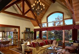 Country Great Room with picture window, Hardwood floors, Chandelier, Wall sconce, Exposed beam, specialty window