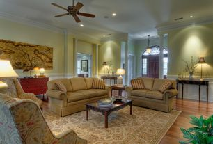 Traditional Living Room with Chair rail, Hardwood floors, High ceiling, Crown molding, Ceiling fan, Columns, Wainscotting