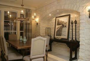 Traditional Dining Room with Crown molding, Arched window, Wall sconce, Concrete floors, Chandelier