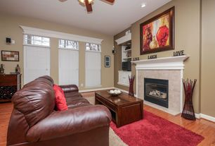 Traditional Living Room with stone fireplace, Built-in bookshelf, Hardwood floors, Ceiling fan