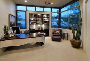 Modern Home Office with Built-in bookshelf, can lights, picture window, flat door, Transom window, High ceiling, Carpet