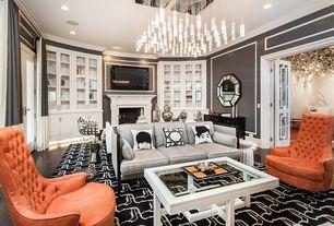 Eclectic Great Room with Built-in bookshelf, Hardwood floors, Chandelier, French doors, stone fireplace, Crown molding