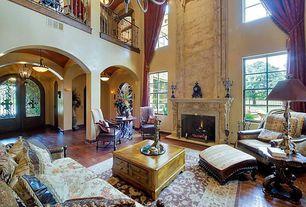 Mediterranean Living Room with Hardwood floors, Cement fireplace, High ceiling, Columns, Chandelier, Loft