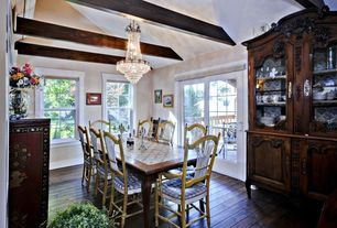 Country Dining Room with Hardwood floors, double-hung window, Exposed beam, Chandelier, Built-in bookshelf, French doors