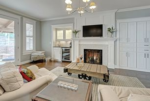 Traditional Living Room with Hardwood floors, Chandelier, French doors, Wood coffee table, Neutral area rug, stone fireplace