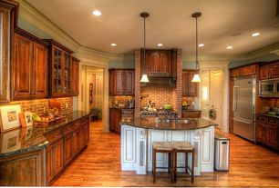 Country Kitchen with Custom hood, specialty door, Simple granite counters, Crown molding, U-shaped, Limestone Tile