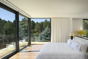 Modern Master Bedroom with picture window, can lights, Standard height, Hardwood floors, sliding glass door