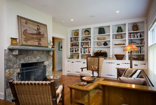 Craftsman Living Room with Fireplace, Built-in bookshelf, double-hung window, Hardwood floors, stone fireplace, can lights
