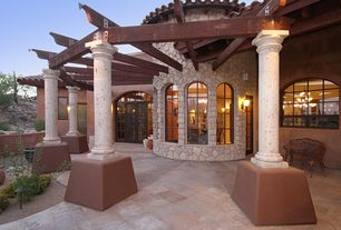 Mediterranean Exterior of Home with exterior stone floors, Arched window, French doors, Fence, specialty window, Trellis