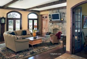 Rustic Living Room with stone fireplace, Arched door, Transom window, Exposed beam, French doors, Oriental area rug