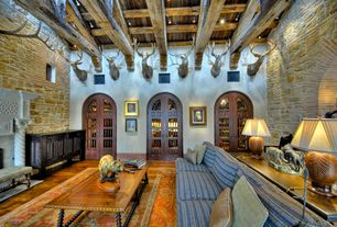 Mediterranean Living Room with Glass panel door, Fireplace, Hardwood floors, High ceiling, stone fireplace, Exposed beam