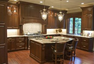 Traditional Kitchen with double oven range, can lights, Complex granite counters, Framed Partial Panel, Limestone Tile