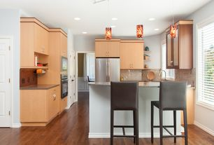 Modern Kitchen with Limestone Tile, Breakfast bar, Galley, Corian counters, wall oven, can lights, built-in microwave, Flush