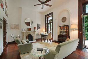 Mediterranean Living Room with Ceiling fan, Cement fireplace, Hardwood floors, Transom window, French doors, High ceiling