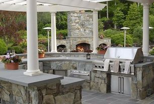 Traditional Patio with Trellis, exterior stone floors, Outdoor kitchen
