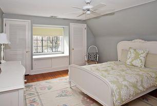 Traditional Guest Bedroom with Ceiling fan, Window seat, Louvered door, Hardwood floors