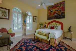 Traditional Guest Bedroom with sandstone floors, Arched window, Ceiling fan