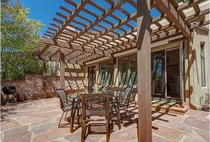 Mediterranean Patio with Trellis, Fence, exterior stone floors, French doors, Casement, Outdoor kitchen
