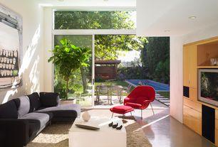 Modern Living Room with Transom window, High ceiling, Built-in bookshelf, sliding glass door, Concrete floors, can lights
