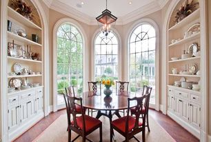 Traditional Dining Room with Built-in bookshelf, Hardwood floors, Pendant light, Arched window, Crown molding