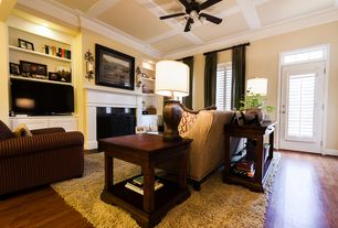 Traditional Living Room with metal fireplace, Box ceiling, Transom window, Crown molding, Hardwood floors, Ceiling fan