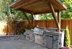 Rustic Patio with Polished concrete, Fence, Outdoor kitchen, Stacked stone, Raised beds, exterior stone floors