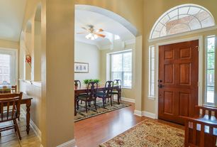 Traditional Entryway with Hardwood floors, High ceiling, Arched window, six panel door