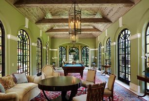 Game Room with High ceiling, Chandelier, Arched window, Exposed beam, French doors, Pendant light, Concrete floors