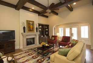 Mediterranean Living Room with Ceiling fan, Built-in bookshelf, Cement fireplace, Box ceiling, Hardwood floors