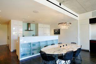 Contemporary Dining Room with Built-in bookshelf, Hardwood floors, Chandelier