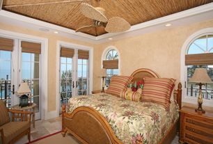 Tropical Master Bedroom with Crown molding, sandstone floors, French doors, Arched window, Ceiling fan