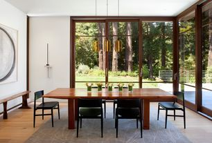 Contemporary Dining Room with Built-in bookshelf, picture window, can lights, Standard height, Hardwood floors, Pendant light