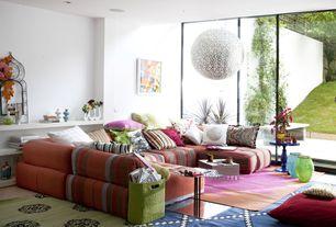 Eclectic Living Room with Chandelier, Built-in bookshelf, sandstone tile floors