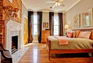 Traditional Master Bedroom with stone fireplace, Hardwood floors, interior brick, Crown molding, Ceiling fan