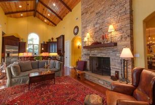Traditional Great Room with Built-in bookshelf, Pendant light, Arched window, stone fireplace, Laminate floors, Exposed beam