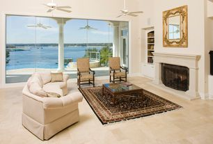 Traditional Living Room with High ceiling, Built-in bookshelf, Ceiling fan, Cement fireplace, limestone tile floors