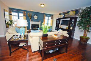 Contemporary Living Room with Hardwood floors, Cement fireplace, Built-in bookshelf, flush light