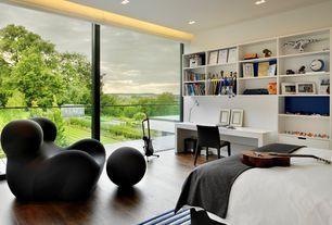 Contemporary Kids Bedroom with B&B Italia Vol Au Vent Chair, Built-in bookshelf, Hardwood floors, Cove lighting