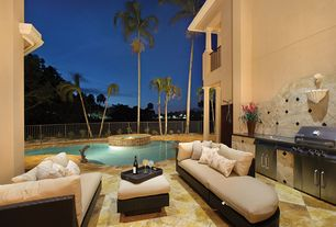 Tropical Patio with Outdoor kitchen, Fence, Pool with hot tub, exterior stone floors