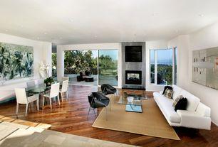 Modern Living Room with Diagonal wood flooring, Aquarium window, Glass coffee table, Hardwood floors, Area rug