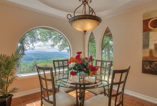 Mediterranean Dining Room with High ceiling, Arched window, terracotta tile floors, Chandelier, Crown molding