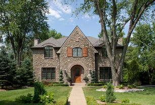 Traditional Exterior of Home with Arched window, Manicured hedges, Pathway, Arched entryway, Natural stone exterior