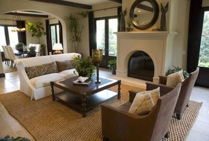 Mediterranean Living Room with limestone tile floors, French doors, Cement fireplace, Exposed beam