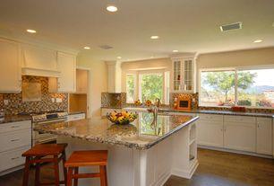 Mediterranean Kitchen with Bay window, Glass panel, Simple granite counters, Breakfast bar, Custom hood, U-shaped, Flush
